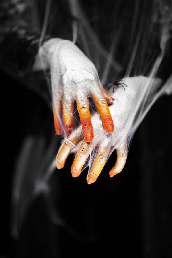 Kusliga halloween händer med rött, apelsinen och silver som täckas i en spindelrengöringsduk med spindlar royaltyfri fotografi