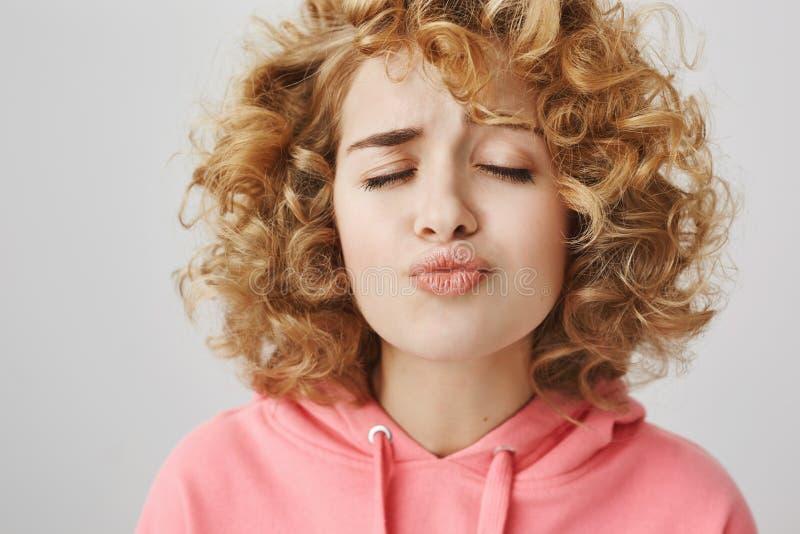 Kuss aber verderben nicht meinen Lippenstift Atelieraufnahme der lustigen und netten gelockten Frau im rosa Hoodie, der Gesicht i stockfoto