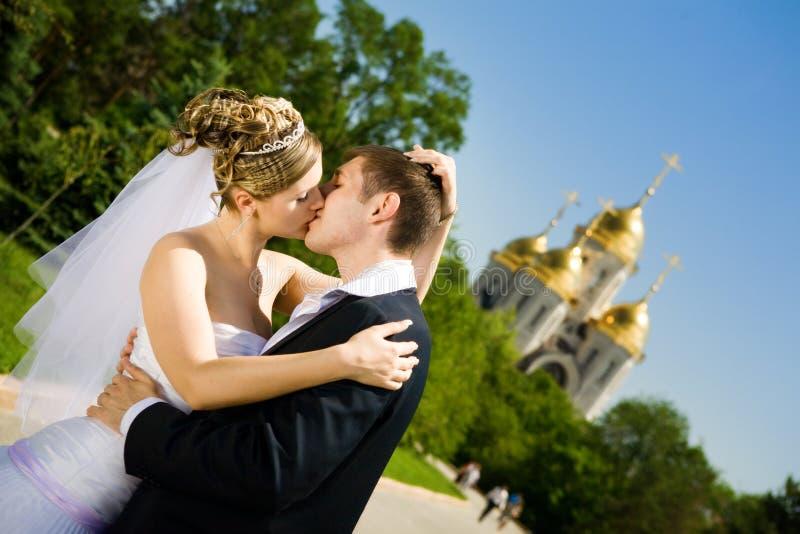 Kuss der Braut und des Bräutigams stockfotos