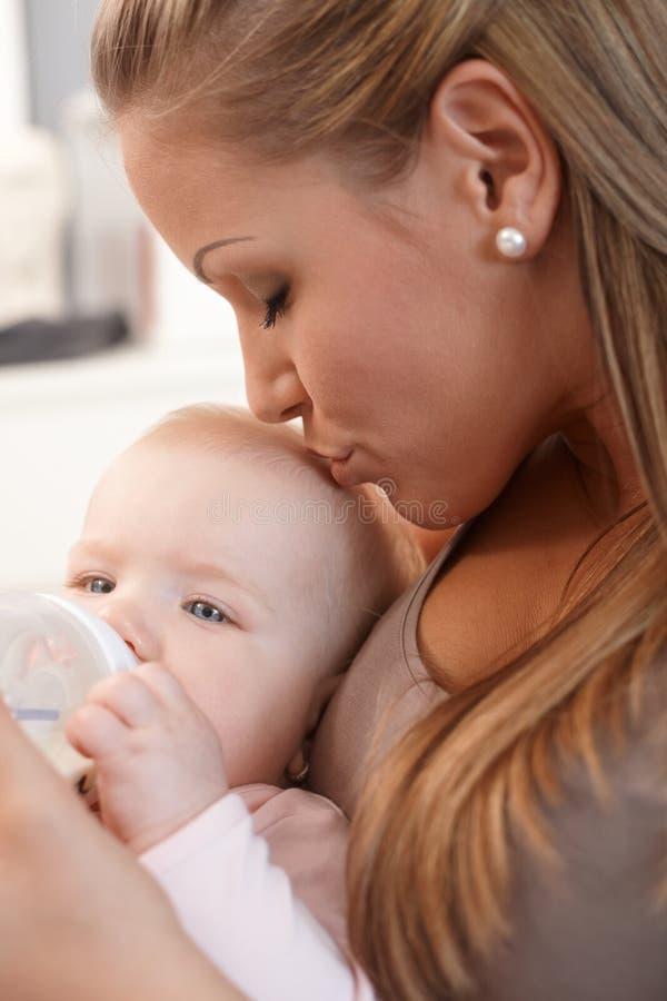 Kussend de babymeisje van de moeder royalty-vrije stock foto's