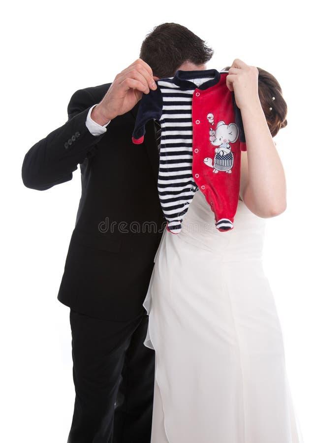 Kussend huwelijkspaar met babykleren: zwangerschap en huwelijk royalty-vrije stock foto's