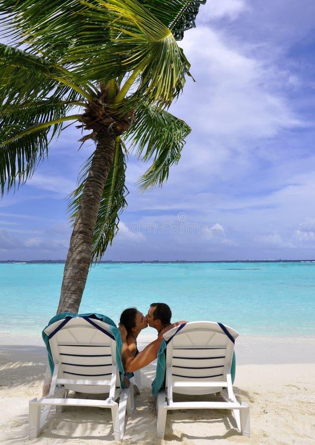 Kussend paar op strand royalty-vrije stock afbeeldingen