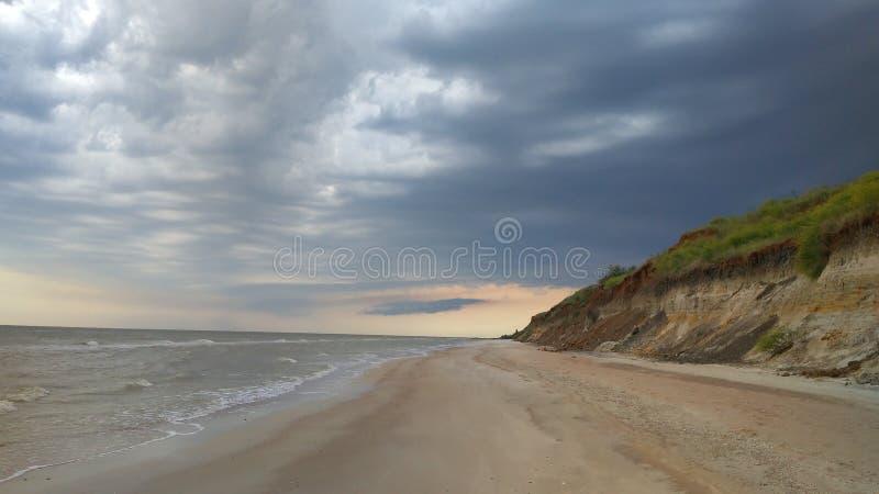 Kust av havet av Azov, pittoreskt landskap med en sandig klippa, en molnig himmel och havsvågor royaltyfria foton
