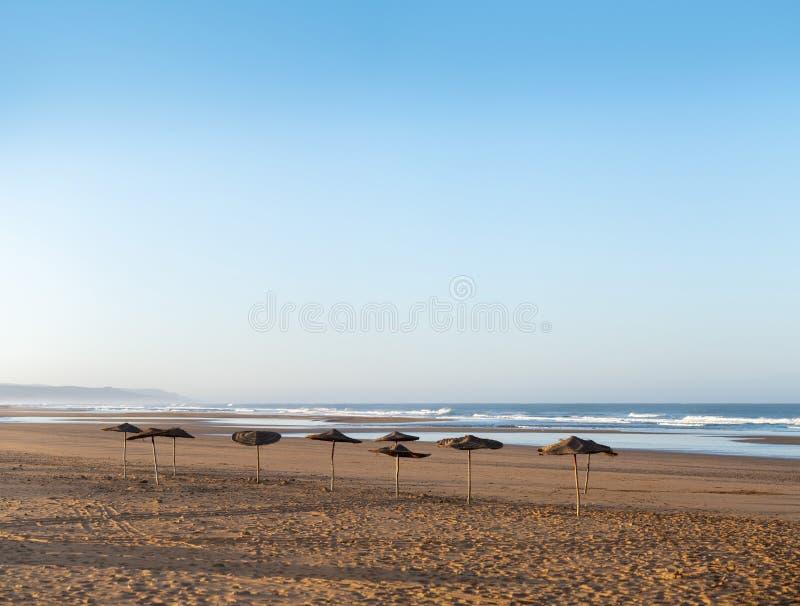 Kust av Sidi Kaouki, Marocko, Afrika Kust med paraplyer Marockos stad för wonderfullbränning royaltyfria foton