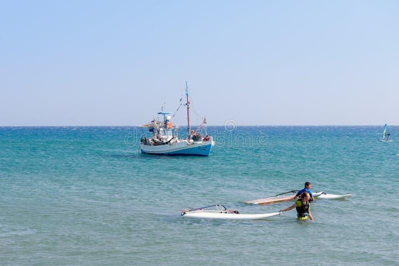 Kust för surfare och för fiskebåt nära av den Rhodes ön arkivbild