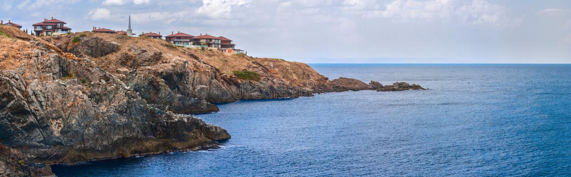 Kust- landskapbaner, panorama - den steniga kusten med byn av Sozopolis royaltyfri fotografi