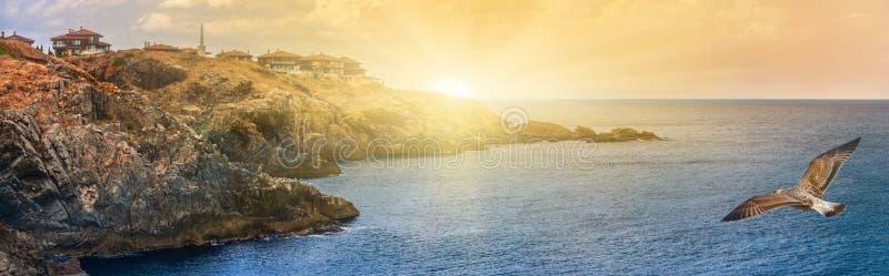 Kust- landskapbaner, panorama - den steniga kusten med seagulls och byn av Sozopolis royaltyfria bilder