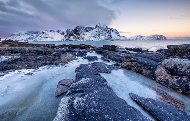 Kust met stenen en ijs tijdens zonsondergang Mooi natuurlijk zeegezicht in de Lofoten-eilanden, Noorwegen royalty-vrije stock foto's