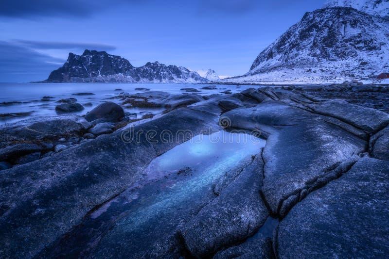 Kust met stenen en vaag water, tegen sneeuwbergen royalty-vrije stock foto's
