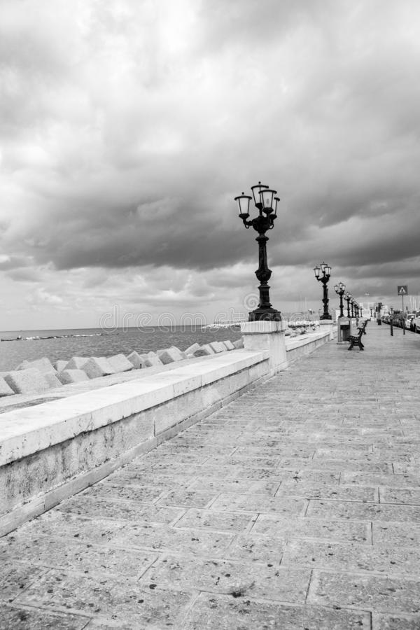 Kust met straatlantaarns in zwart-wit perspectief Adriatisch zwart-wit zeegezicht Italiaanse kustlijn royalty-vrije stock foto's