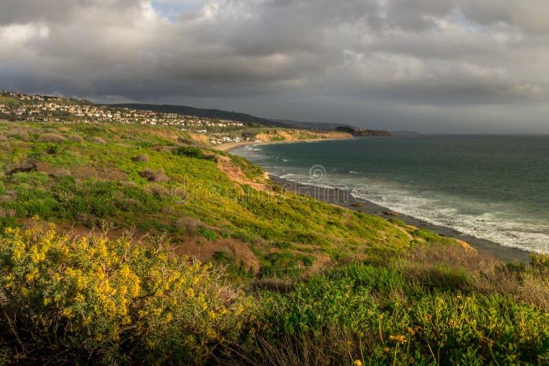 Kust- sikt av Laguna Beach, Kalifornien under dramatiska moln på den guld- timmen från Crystal Cove State Park royaltyfri bild
