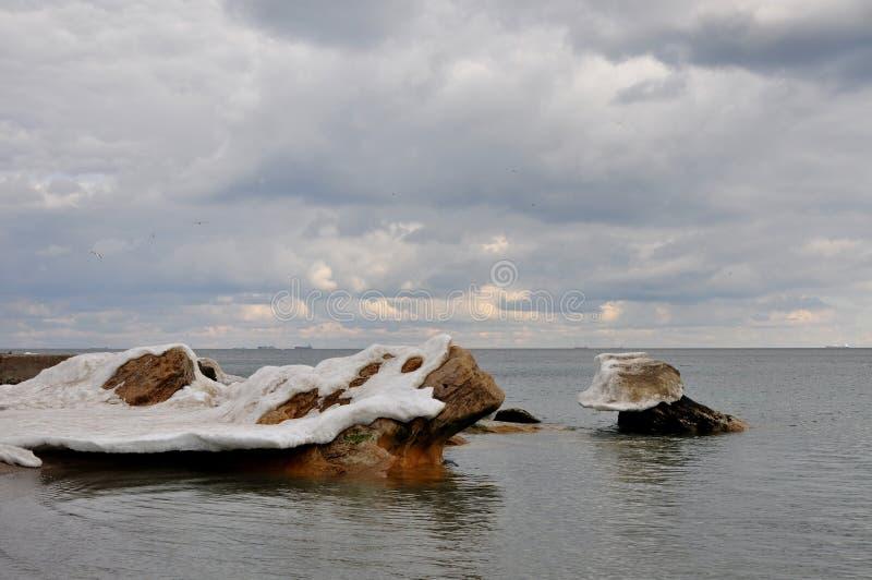 Kust- stenar i det Black Sea pipet ut från under tillväxterna av smältande snö och is arkivfoton