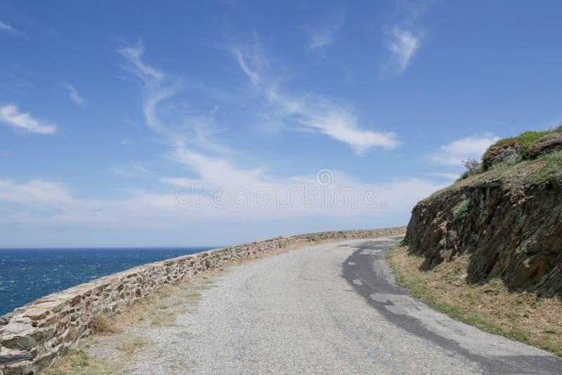 Kust- väg, stigande krökt väg med havsikt och molnig blå himmel arkivfoton