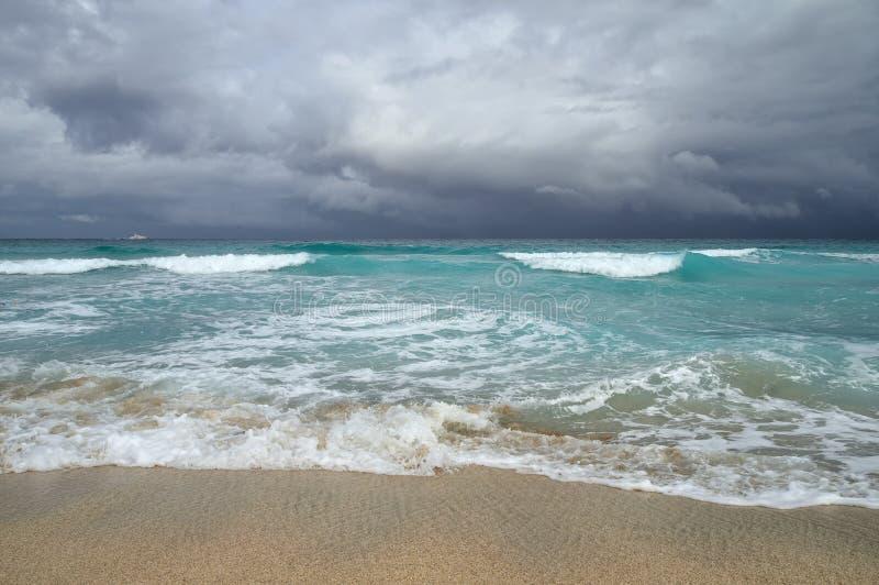 Kust van de Atlantische Oceaan tijdens een onweer, golven op het zand, motorjacht op de horizon, lage wolken, Varadero, Cuba stock afbeeldingen