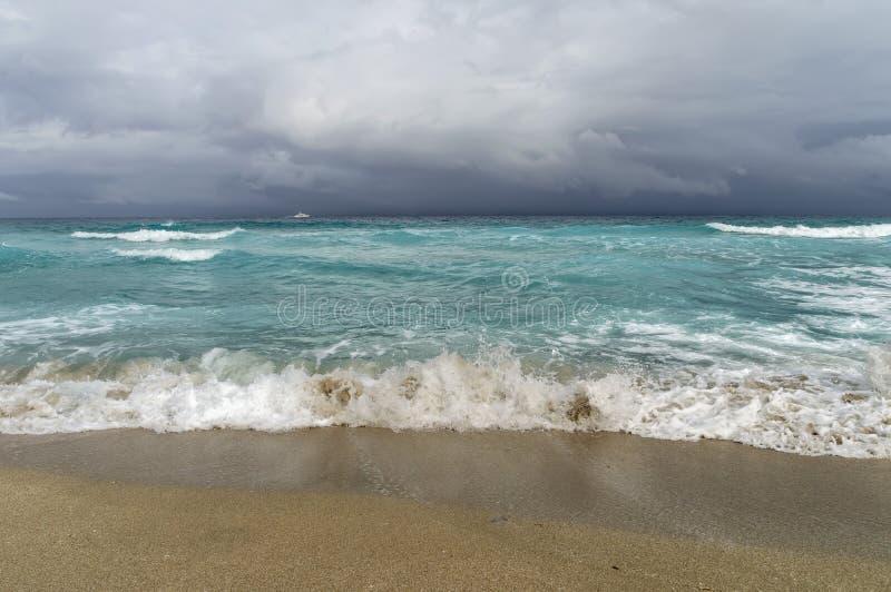Kust van de Atlantische Oceaan tijdens een onweer, een wit motorjacht op de horizon, royalty-vrije stock afbeelding