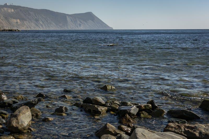 Kust van de Zwarte Zee bij zonsondergang Overzeese stenen en rotsen van verschillende grootte en texturen royalty-vrije stock fotografie