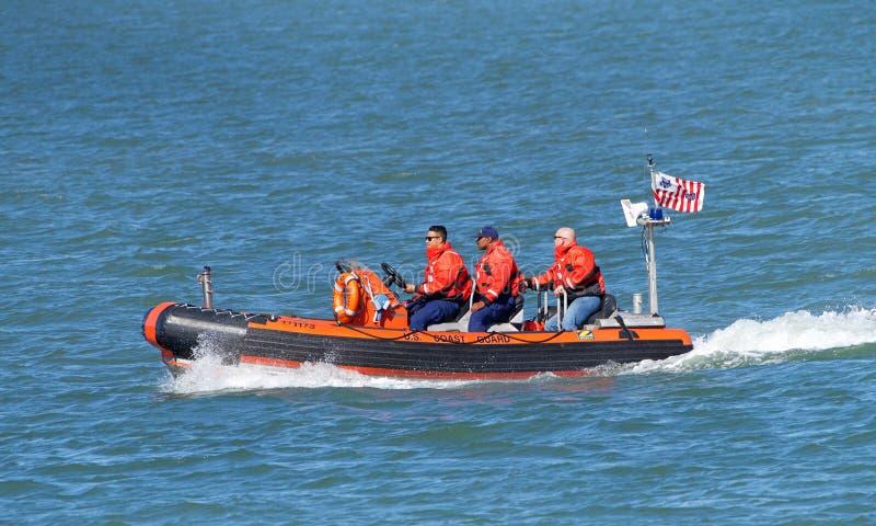 Kustbevakningfartyg med besättningen i vatten arkivfoton