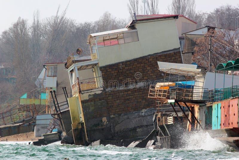 Kustdieerosie - huizen op de zwakke dia van de kleigrond neer aan overzees worden gebouwd stock afbeeldingen