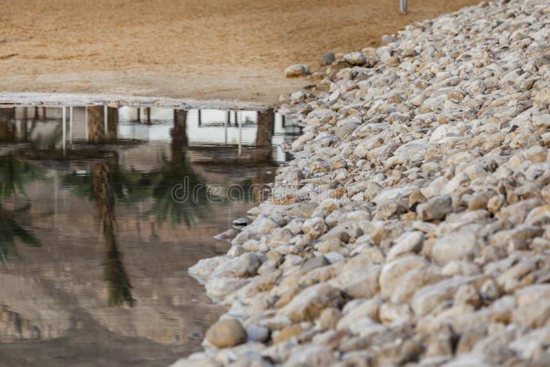 Kusten för steninvallningsand och gömma i handflatan reflekterat i vatten royaltyfri foto