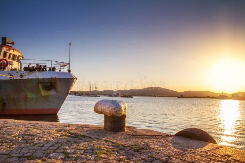 Kustlandschap - mening van de pijler met een vastgelegd schip in zonsondergangtijd stock afbeeldingen