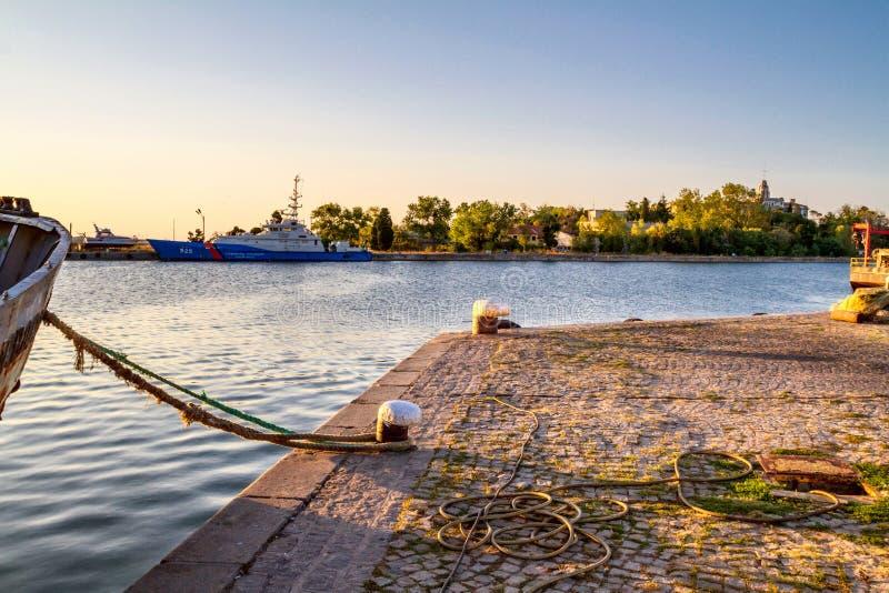 Kustlandschap - mening van de pijler met een vastgelegd schip in zonsondergangtijd royalty-vrije stock foto