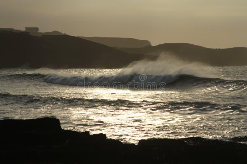 Kustlinjen med vaggar, stora inkommande vågor med havssprej under solnedgång arkivbilder
