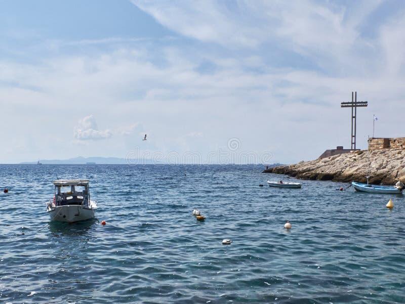 Kustlinjen Saronic gulf, Egeiska havet, båt och minneskorsningen vid Pireus, Attika, Grekland arkivbilder