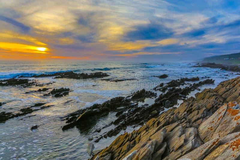 Kustzonsondergang en Overzees met Rotsen en Wolken royalty-vrije stock afbeelding