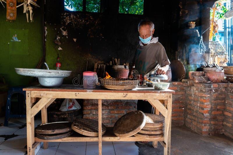 KUTA/BALI- 28 DE MAR?O DE 2019: O processo de fazer bolos tradicionais do Balinese chamou Kue Laklak por um anci?o com fornalha d foto de stock royalty free