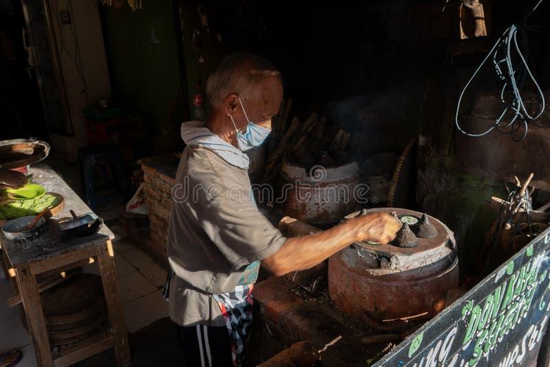 KUTA/BALI- 28 DE MAR?O DE 2019: O processo de fazer bolos tradicionais do Balinese chamou Kue Laklak por um anci?o com fornalha d fotos de stock royalty free