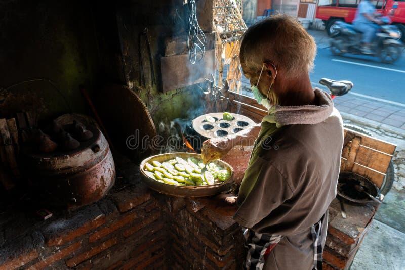 KUTA/BALI- 28 DE MAR?O DE 2019: O processo de fazer bolos tradicionais do Balinese chamou Kue Laklak por um anci?o com fornalha d fotos de stock