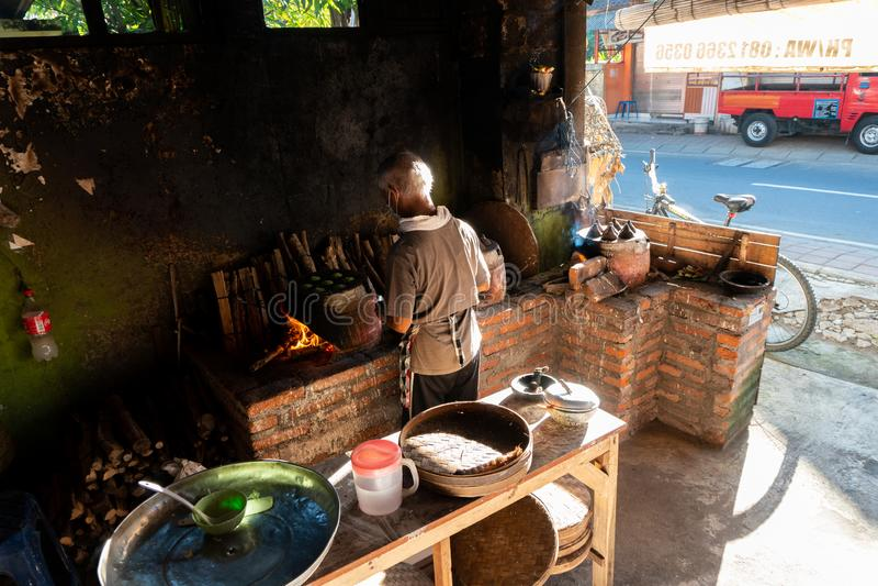 KUTA/BALI- 28 DE MAR?O DE 2019: O processo de fazer bolos tradicionais do Balinese chamou Kue Laklak por um anci?o com fornalha d foto de stock