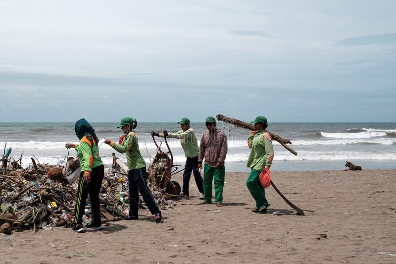 Kuta, BALI INDONESIA - 27 gennaio 2018 la gente che raccoglie immondizia sulla spiaggia immagine stock libera da diritti