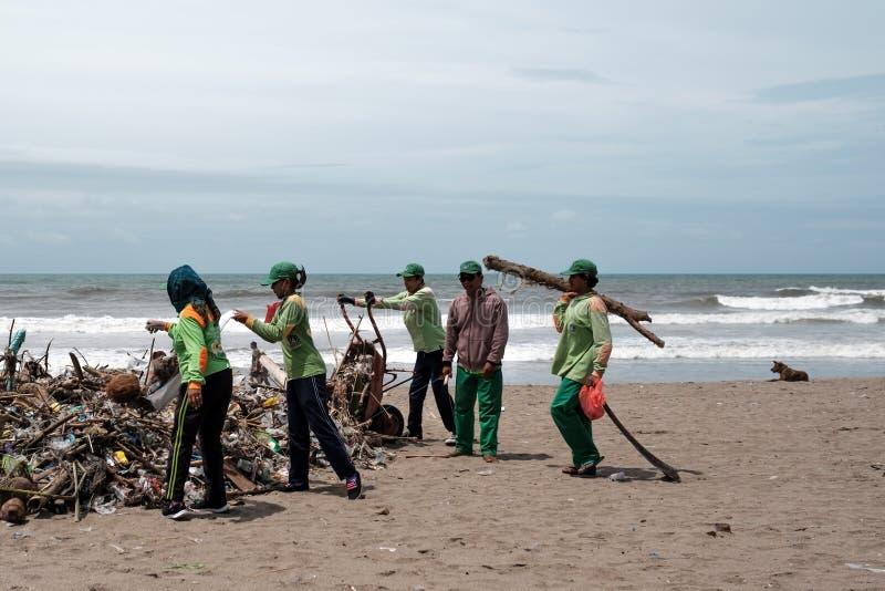 Kuta BALI INDONESIEN - Januari 27, 2018 personer som samlar avskräde på stranden royaltyfri bild