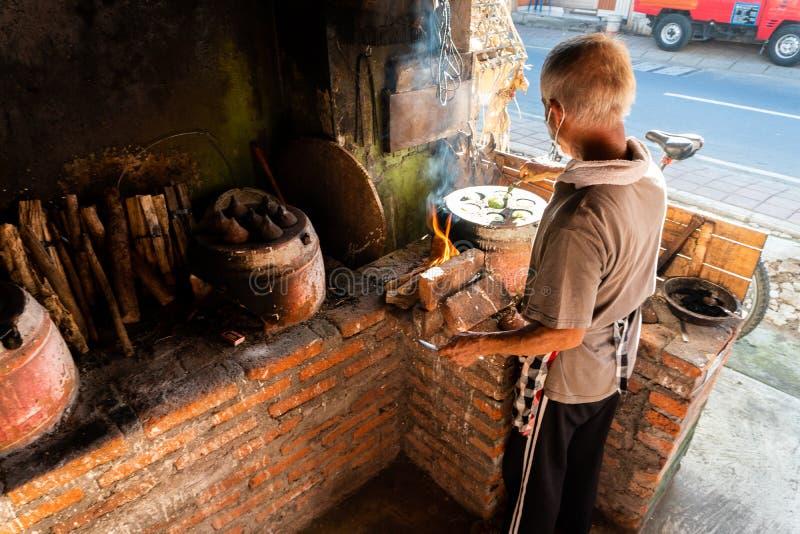 28 kuta/bali-MAART 2019: Het proces om traditionele Balinese cakes te maken riep Kue Laklak door een oude mens met kleioven stock afbeelding