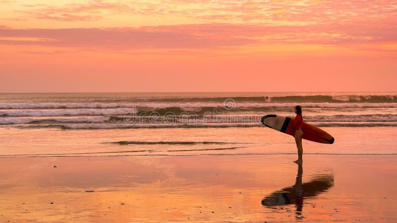 KUTA, INDONESIA - JUNIO, 15, 2017: una muchacha con un longboard mira la resaca en la playa del kuta, Bali imagen de archivo