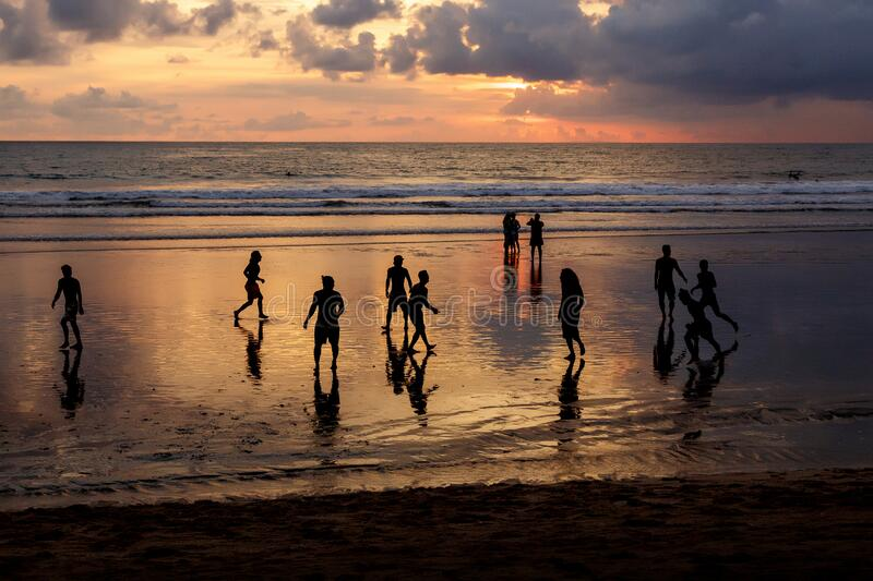 Kuta, Indonesia - March 25, 2019 : Silhouette of locals playing football at sunset.  stock photos
