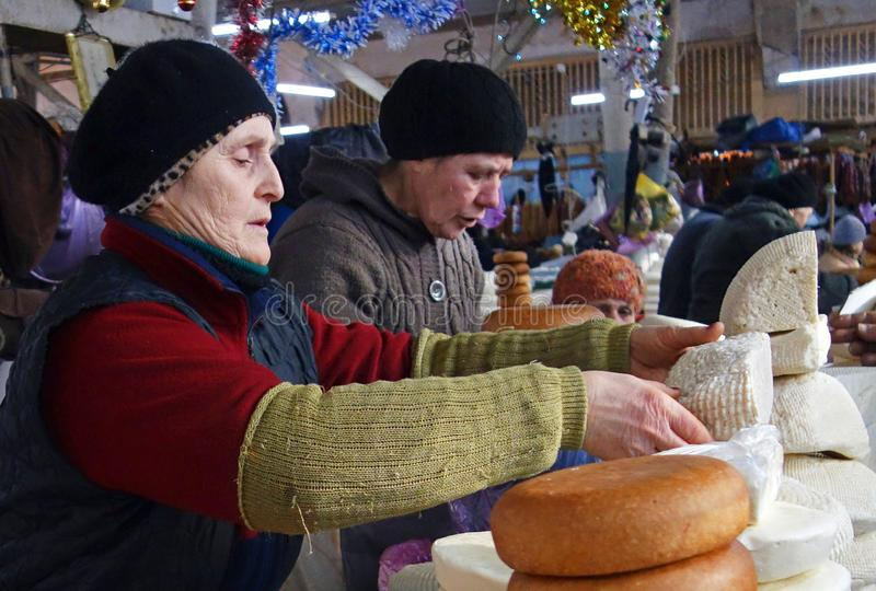 KUTAISI, GEORGIA - January 3, 2017: Women selling homemade and smoked cheese on big food market. Traditional Caucasian homemade cheese sulguni. Market, Georgia royalty free stock images