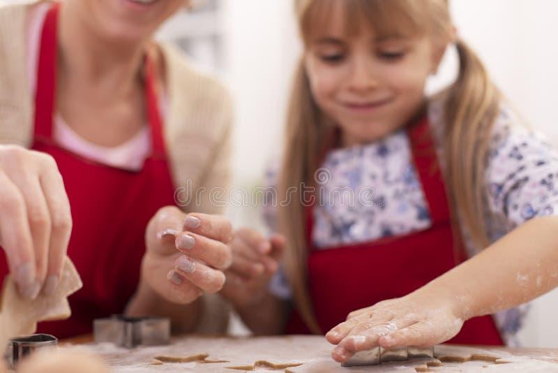 Kute girl die broodkoekjes snijdt uit het gespannen deeg - haar moeder helpt en helpt stock fotografie