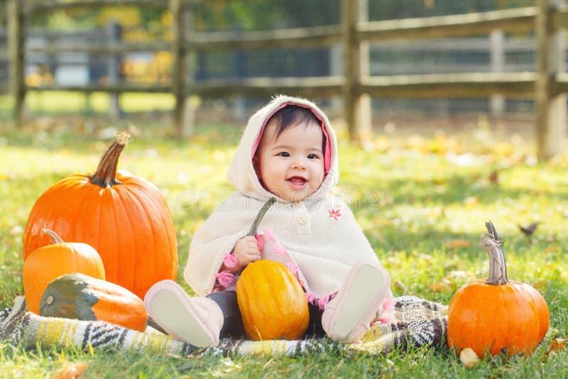 Kute grappige, grappige, Aziatische baby meisje in de herfstherfstherfstpark in de openlucht met gele oranje pompoenen royalty-vrije stock fotografie