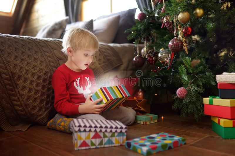 Kute jongen die een kerstcadeau opent Portret van gelukkig kind op kerstochtend royalty-vrije stock foto