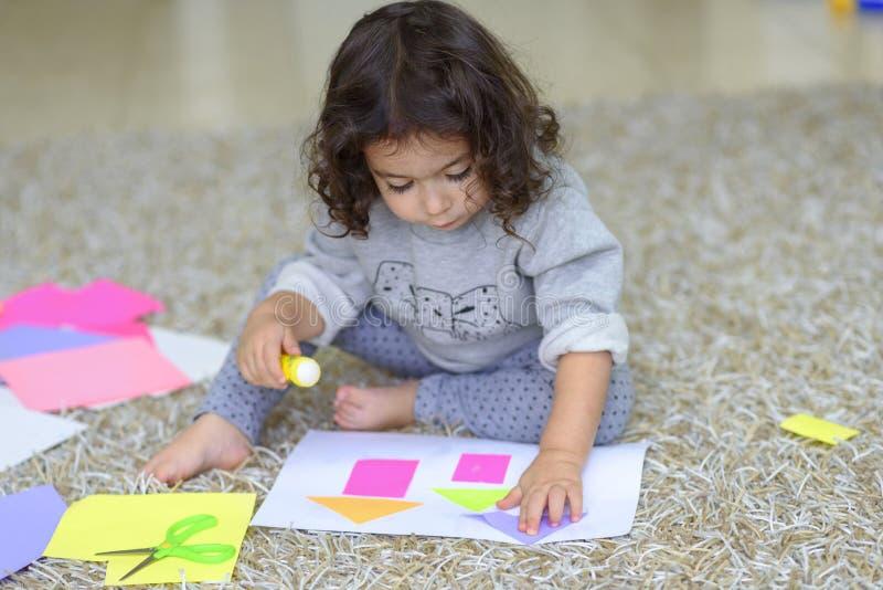Kute kindje maakt een appel, lijm een kleurrijk huis stock afbeeldingen