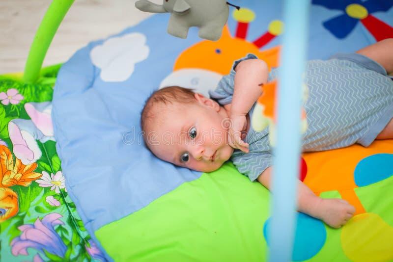 Kute pasgeboren caucasiaanse baby ligt op zijn rug om mat te ontwikkelen en speelgoed selectief te bekijken stock afbeelding