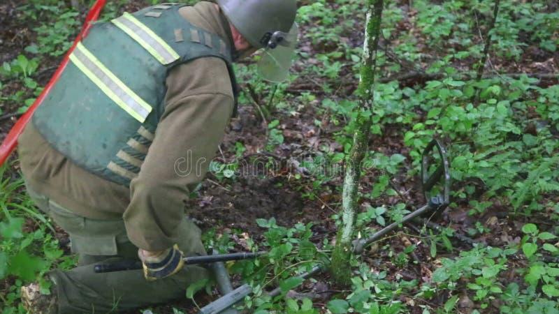 KUTINA KROATIEN - JUNI 2014: Man som försöker att avkänna minen i minröjningprocess i mitt av skogen arkivfilmer