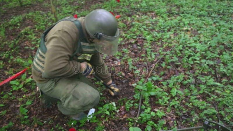 KUTINA KROATIEN - JUNI 2014: Man som försöker att avkänna minen i minröjningprocess i mitt av skogen lager videofilmer
