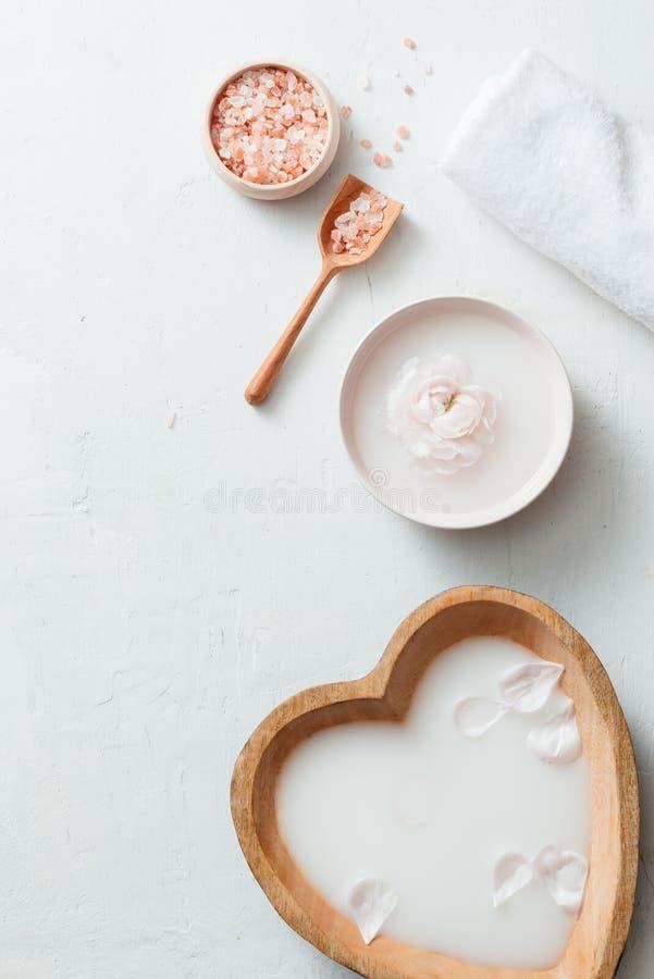 Kuuroord die met de kom, de bloemen, het zout, de zeep, de olie en de handdoek van de rijstmelk op witte achtergrond plaatsen stock afbeelding