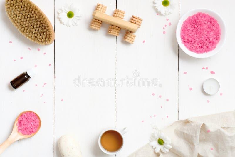 Kuuroord die met lichaamsborstel plaatsen, roze badzout, handdoek, organische komeetzeep, etherische olie op houten achtergrond,  royalty-vrije stock foto's