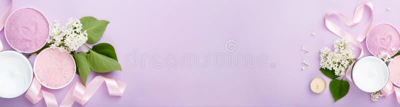 Kuuroord en huid de banner van zorgproducten roomt, en overzees badzout op purpere achtergrond met de lente witte lilac bloesem a stock foto's