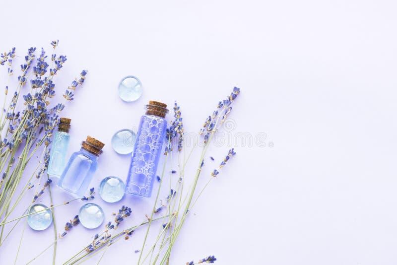 Kuuroord en wellness die met lavendel het plaatsen bloeien, overzees zout, olie in een fles, aromakaars op houten witte achtergro royalty-vrije stock afbeelding