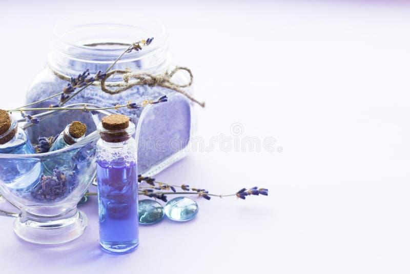 Kuuroord en wellness die met lavendel het plaatsen bloeien, overzees zout, olie in een fles, aromakaars op houten witte achtergro royalty-vrije stock foto's